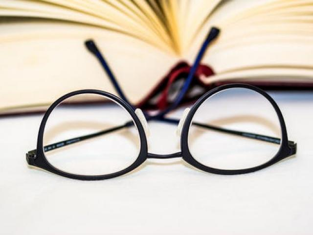 pair of eyeglasses lying in front of an open book